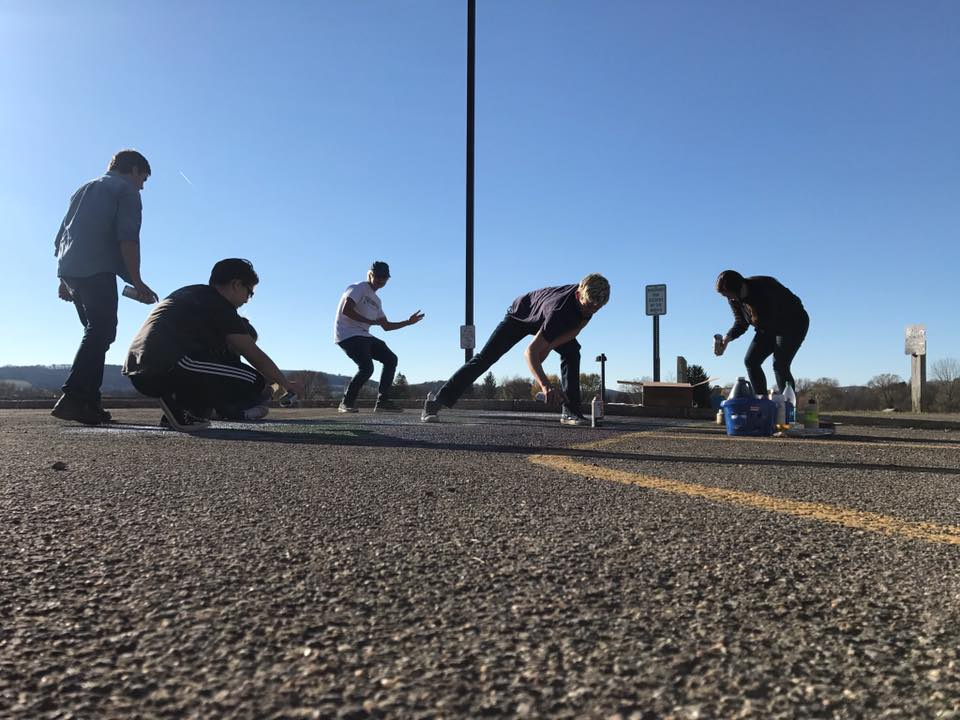 Students paint a parking spot.