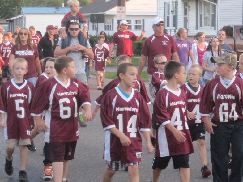 pee wee football players march in the homecoming parade