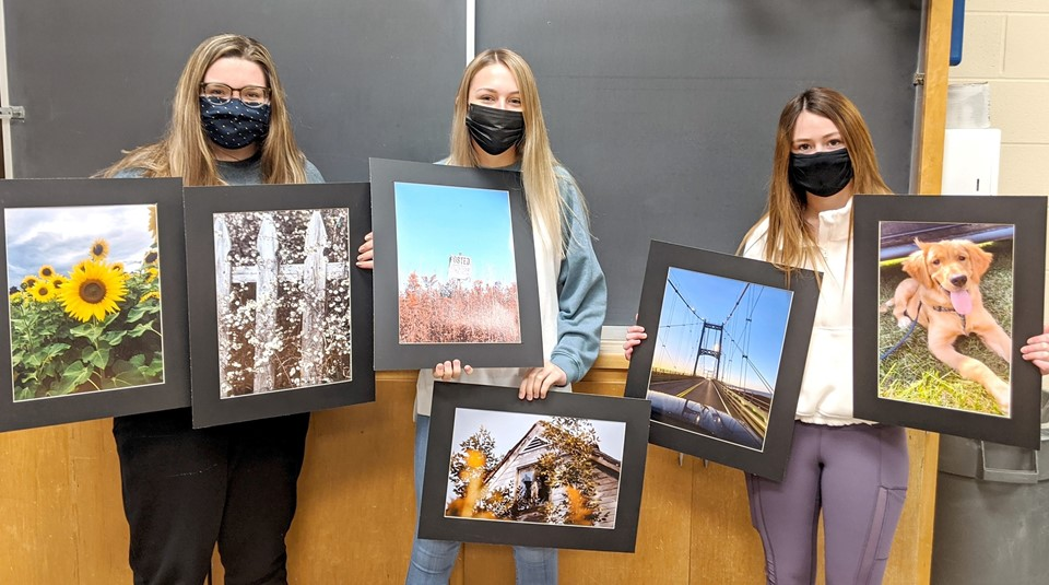Three female students holding artwork (2/2021)